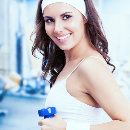 Portrait of young brunette woman exercising with dumbbell, at fitness center or gym. Individual sports, training, workout, exercising, aerobics and healthy lifestyle concept. Female instructor. Square composition. Stock Photo
