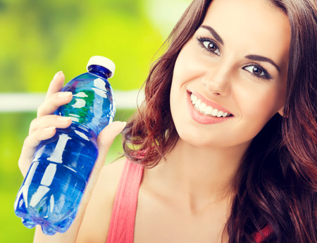 Portrait of young happy woman with bottle of water