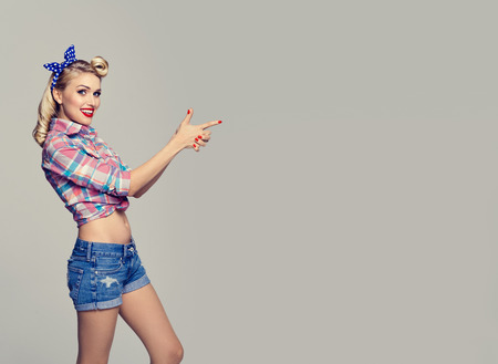 Young happy smiling woman, dressed in pin-up style, showing something or copyspace area for text or slogan. Caucasian blond model posing in retro fashion and vintage concept studio shoot. Stock Photo