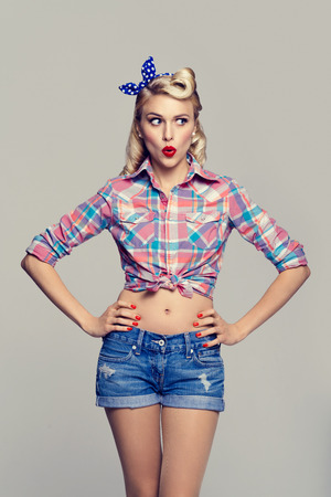 Portrait of beautiful young surprised woman, dressed in pin-up style. Caucasian blond model posing in retro fashion and vintage concept studio shoot. Stock Photo