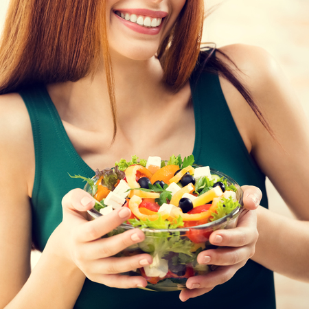 Portrait of happy smiling young woman with vegetarian vegetable salad, indoors or at home. Beauty and dieting concept. Weight lossing, by healthy eating. Square composition.