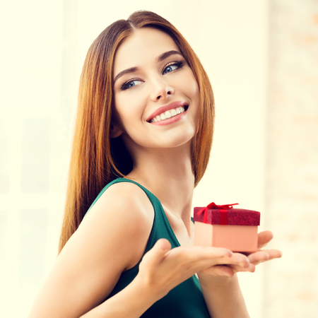 Caucasian woman: Young happy smiling woman with gifts, at home, indoors. Celebration and holiday sale concept with caucasian beautiful model. Square composition.