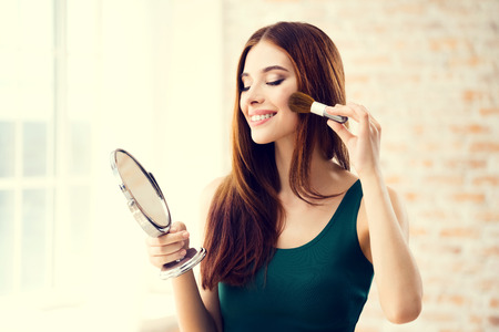 make up brush: Young woman with mirror and makeup brush indoors. Beautiful caucasian model in make up and beauty treatment concept shoot.