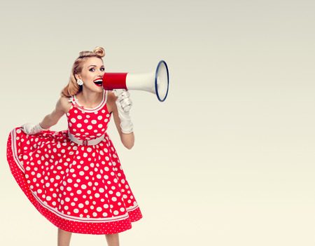 Portrait of woman holding megaphone, dressed in pin-up style red dress in polka dot and white gloves. Caucasian blond model posing in retro fashion vintage studio shoot. Copyspace area for advertising slogan or text message. Stock Photo