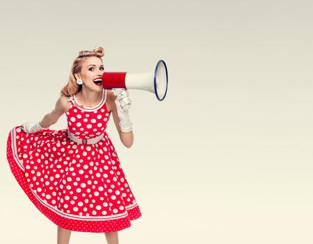 Retrato de la mujer que sostiene el megáfono, vestido en estilo de pin-up vestido rojo en punto de polca y guantes blancos. Caucásicos modelo rubia posando en la moda retro disparo de estudio vintage. Área de Copyspace para el lema de la publicidad o el mensaje de texto. Foto de archivo - 65574261