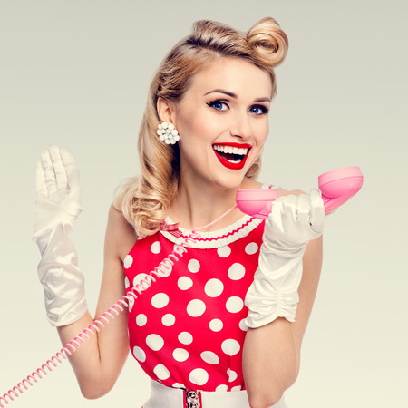 good grooming: Funny portrait of beautiful happy woman with phone, dressed in pin-up style red dress in polka dot and white gloves. Caucasian blond model posing in retro studio shoot. Stock Photo