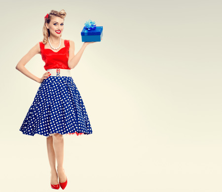 Full body portrait of smiling woman dressed in pin-up style dress with polka dot. Caucasian blond model posing in retro fashion and vintage concept studio shoot. Copyspace area for advertising slogan or text message. Stock Photo