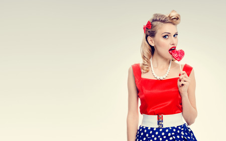 eating area: Portrait of woman eating heart shape lollipop dressed in pinup style dress in polka dot. Caucasian blond model posing in retro fashion and vintage concept studio shoot. Copyspace area for advertising slogan or text message.