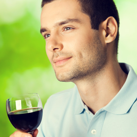 males only: Thinking young man with glass of red wine, outdoors. Square composition.