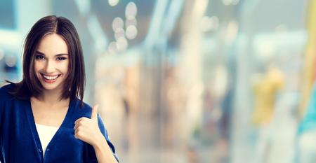 retail shopping: Smiling beautiful young woman in casual smart blue clothing, showing thumbs up gesture, at shopping centre or mall. Caucasian model in sales, shop, retail, consumer concept. Stock Photo