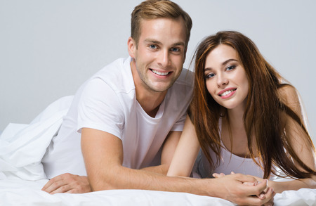 Portrait of young attractive happy couple on the bed at bedroom. Caucasian models in love, relationship, dating, happy people, bedtime concept shot.