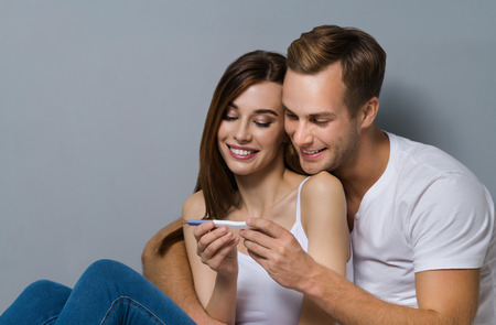 finding out: Beautiful young amorous couple, finding out results of a pregnancy test. Caucasian white models - in love, relationship, dating, happy lovers, concept shot, against grey background.