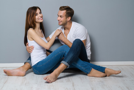 Full body portrait of beautiful young couple, sitting on floor, looking at each other with smile. Caucasian models - in love, relationship, dating, happy lovers, concept shot, against grey background.