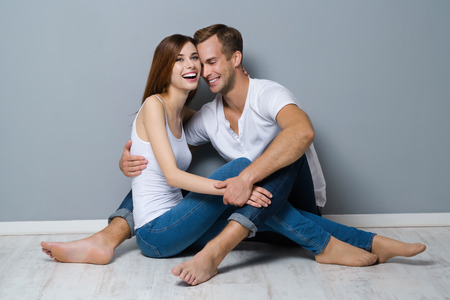 young happy couple: Full body portrait of beautiful young laughing couple, sitting on floor, close to each other. Caucasian white models in love, relationship, dating, happy lovers, concept shot, against grey background. Stock Photo