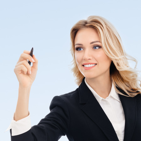 glassboard: Happy smiling cheerful young businesswoman writing or drawing something on screen or transparent glass, by blue marker, on blue background. Caucasian blond model in business success concept.
