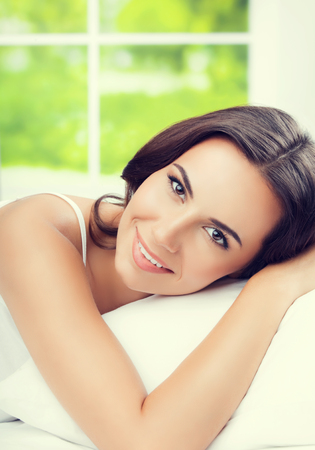 Young beautiful woman waking up with pillow, at bedroom. Brunette model in healthy lifestyle concept shot. Stock Photo