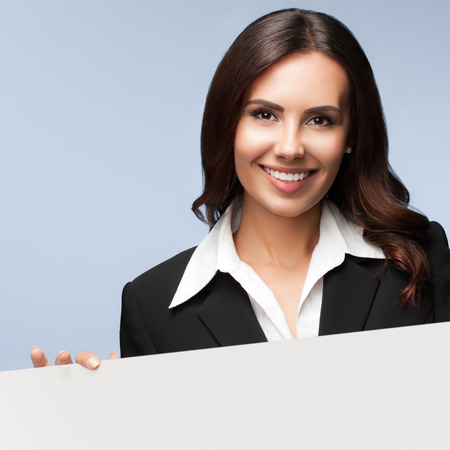 motto: Portrait of happy smiling young businesswoman in black suit, showing blank signboard with copyspace empty area for slogan or advertise text. Brunette model in business success concept shot. Stock Photo