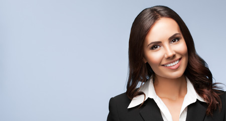 belle brunette: Portrait of happy smiling beautiful young businesswoman, on grey background. Brunette model in black suit - business success concept. Copyspace empty area for some text message or advertise slogan.