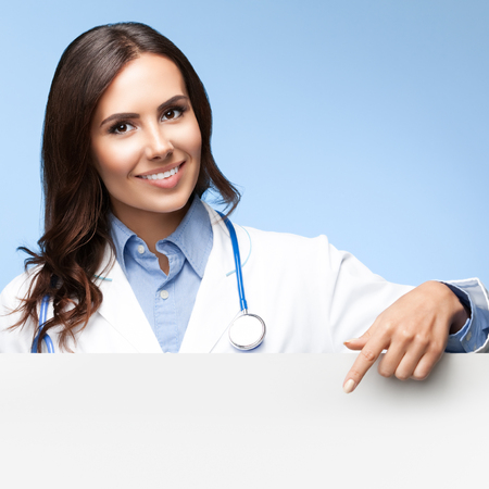 medicaid: Portrait of happy smiling female doctor showing blank signboard with copyspace for slogan or advertise text, on bright blue background. Healthcare, medical, lab consulting and exam concept.