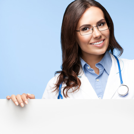 Portrait of happy smiling female doctor in glasses, showing blank signboard with copyspace for slogan or advertise text, on bright blue background. Healthcare, medical, lab consulting and exam concept.