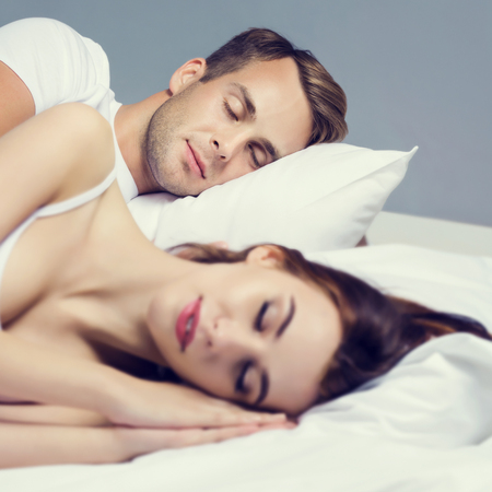 enamorados en la cama: Young couple sleeping on the bed in bedroom. Caucasian models - in love, relationship, dating, happy people, bedtime concept shot.