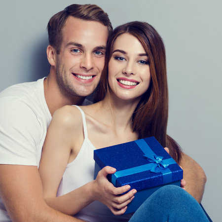 Young amorous smiling couple holding blue gift box, sitting close to each other and looking at camera. Caucasian white models -love, relationship, dating, happy lovers, concept, over grey background.