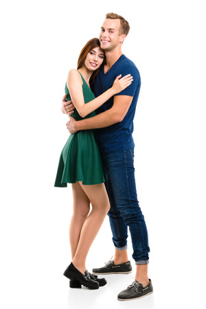 Full body portrait of young happy hugging couple, standing close to each other and looking at camera with smile. Caucasian models in love, relationship, dating, flirting, lovers, romantic concept, isolated against white background.