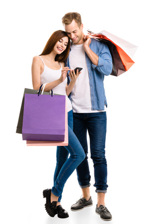 Happy couple with shopping bags, and cellphone, standing close to each other with smile. Caucasian models in love, holiday sales, shop, retail, consumer concept, isolated on white background. Stock Photo