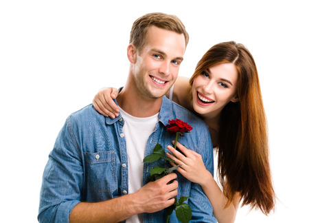 giving back: Portrait of young happy hugging couple with rose, close to each other, with smile. Caucasian models in love, relationship, dating, flirting, lovers, romantic concept, isolated over white background.
