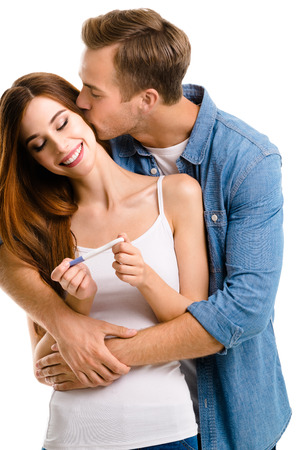 finding out: Young amorous happy couple, finding out results of a pregnancy test. Caucasian models - in love, relationship, dating, happy lovers, family concept, isolated on white background.
