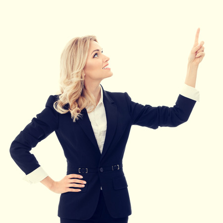 woman pointing: Happy smiling young businesswoman, showing something, some product or blank copyspace area for advertise slogan or text message. Caucasian blond model in business success concept.