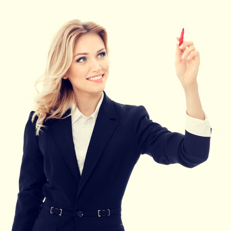 glassboard: Happy smiling cheerful young businesswoman writing or drawing something on screen or transparent glass, by red marker. Caucasian blond model in business success concept.