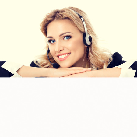 phone operator: Call center. Customer support service phone operator in headset showing signboard with copyspace area for text or advertise slogan. Caucasian blond model in business success concept.