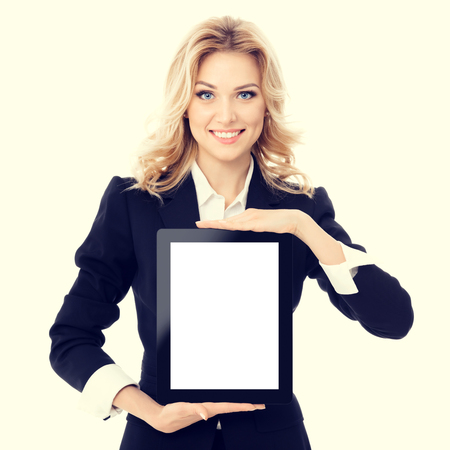 Portrait of smiling beautiful young businesswoman showing blank no-name tablet pc monitor with copyspace area for slogan or text message. Caucasian blond model in business concept shoot.