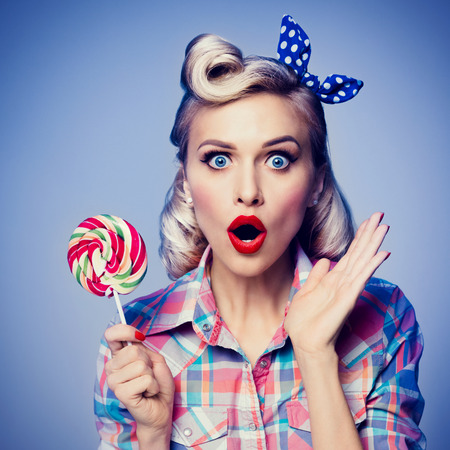 the sixties: Portrait of beautiful woman with lollipop, dressed in pin-up style. Caucasian blond model posing in retro fashion and vintage concept studio shoot, blue background Stock Photo
