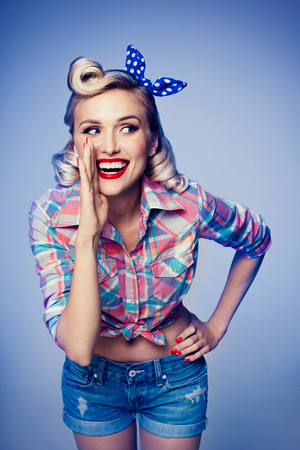 good grooming: Portrait of beautiful young happy smiling woman, dressed in pin-up style. Caucasian blond model posing in retro fashion and vintage concept studio shoot, on blue background. Stock Photo