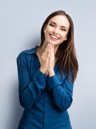 Retrato de gesticular feliz de la mujer joven y sonriente en la ropa informal elegante azul, sobre fondo gris. modelo morena caucásico en emoshions y, sentimiento de felicidad tiro del estudio del concepto optimista, positivo. Foto de archivo