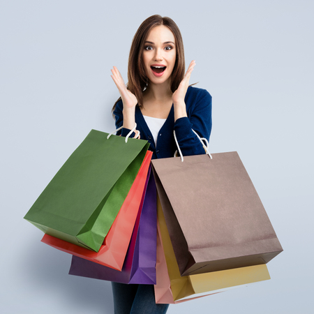 clothing model: Portrait of happy gesturing smiling young woman in casual smart blue clothing, on grey. Caucasian model in sales, shop, retail, consumer concept. Square composition.