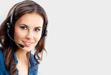 sho: Portrait of happy smiling cheerful beautiful young female support phone operator in headset, over grey background, with blank copyspace area for advertising slogan or text message. Caucasian brunette model in help servise and client consulting concept sho