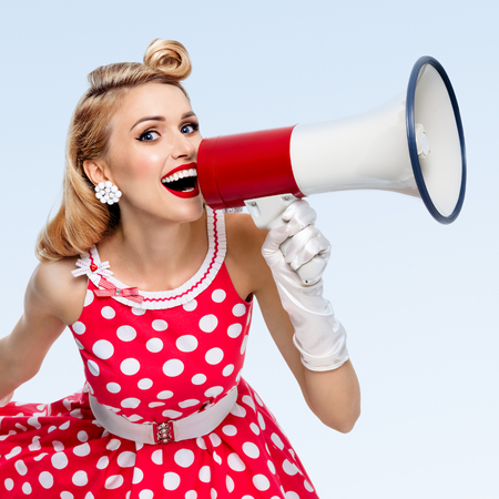 Porträt von Frau mit Megaphon, gekleidet in Pin-up-Stil roten Kleid in Polka Dot und weißen Handschuhe, auf blauem Hintergrund. Kaukasischen blonden Modell posiert in Retro-Mode Vintage Studio schießen.