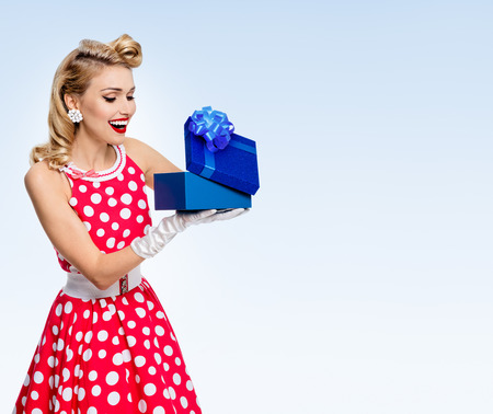 Happy woman in pin-up style red dress in polka dot, on blue background, with blank copyspace area for advertise text or slogan. Caucasian blond model posing in retro fashion concept studio shoot.