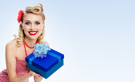 Young happy smiling woman in pin-up style clothing, on blue background, with blank copyspace area for advertise text or slogan. Caucasian blond model posing in retro fashion and vintage concept. Stock Photo
