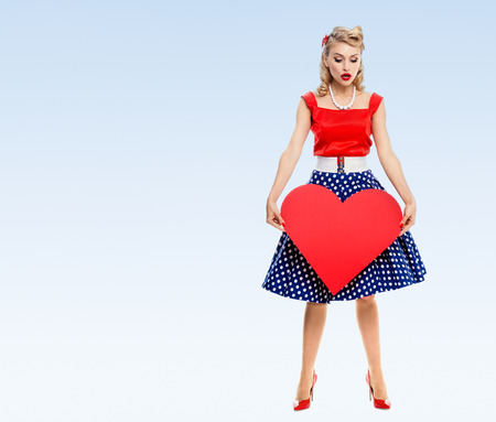fond de texte: Full body of woman holding heart symbol, in pin-up style, on blue background, with blank copyspace area for advertise text or slogan. Caucasian blond model posing in retro fashion and vintage concept.