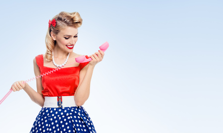Beautiful woman with phone in pin-up style dress with polka dot, on blue, with blank copyspace area for advertise text or slogan. Caucasian blond model posing in retro fashion and vintage concept.