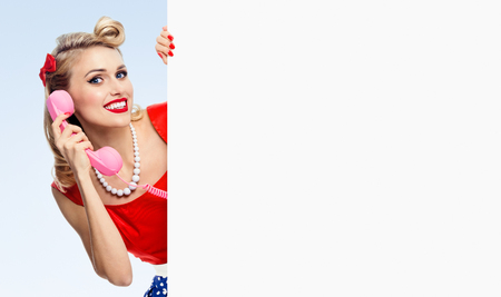 Woman with phone, in pin-up style dress, showing blank signboard with copyspace area, on blue background. Caucasian blond model posing in retro fashion and vintage concept studio shoot.