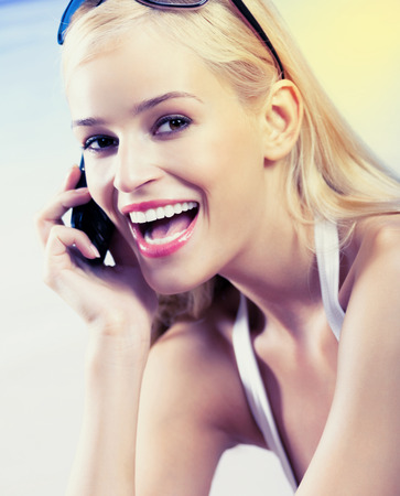 ef6eadd6510 #65643611 - ビーチでの携帯電話で幸せな笑顔の若い美しい女性の肖像画