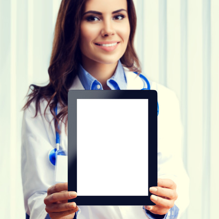 Portrait of happy smiling young female doctor showing no-name tablet pc with blank copyspace area for slogan or advertise text, at office. Selective focus on tablet pc. Healthcare, medical, online help, lab consulting and exam concept.