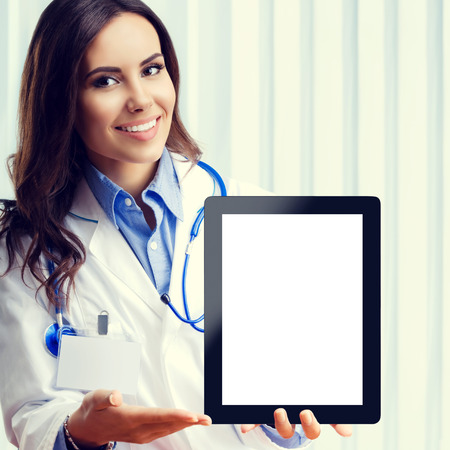 Happy smiling young doctor showing no-name tablet pc with blank copyspace area for slogan or advertise text, at office. Healthcare, medical, online help, lab consulting and exam concept.