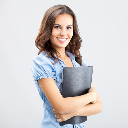 Portrait of happy smiling young cheerful businesswoman with black folder, over grey background. Caucasian brunette model in business concept studio shoot.