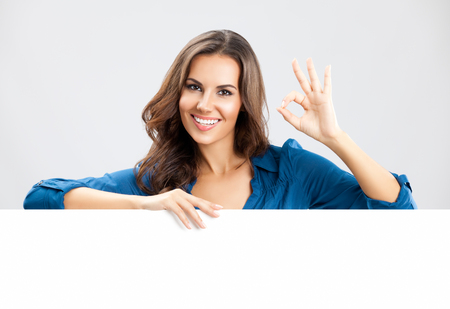 Happy smiling beautiful young business woman showing blank signboard with empty copyspace area for slogan or advertising text message, on grey background. Stock Photo